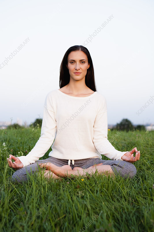 Smiling woman meditating in park