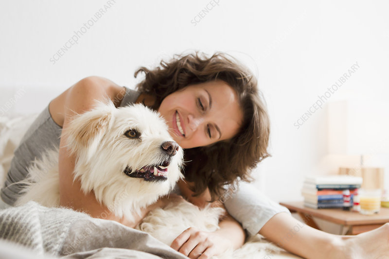 Smiling woman petting dog in bed