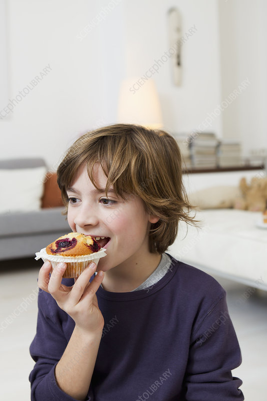 Boy eating muffin in living room