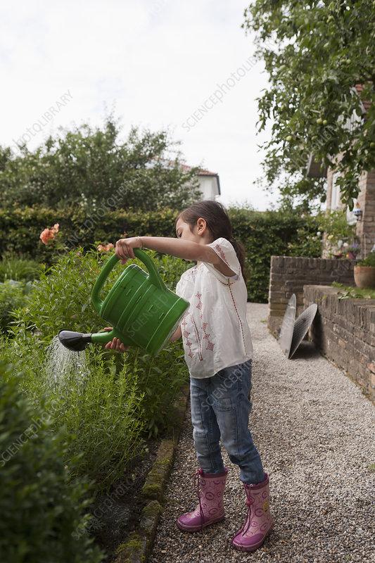 Girl watering plants in backyard