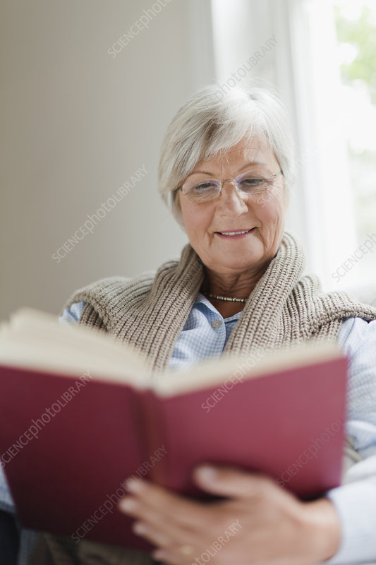 Smiling older woman reading book