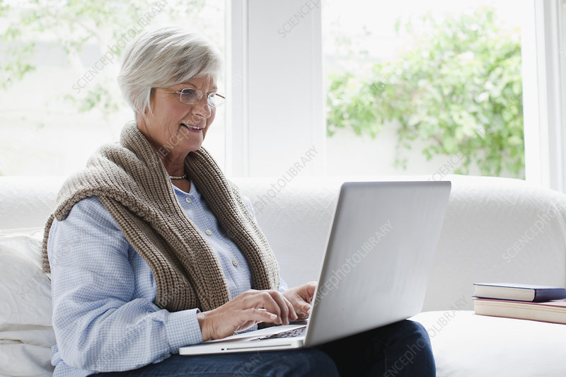 Smiling older woman using laptop