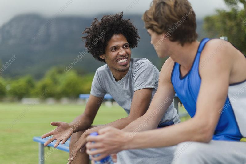 Men talking on bleachers in park