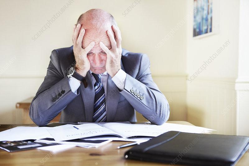 Businessman reading notes at desk