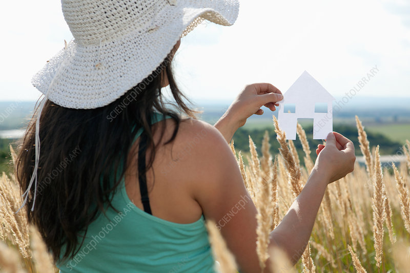 Woman holding paper house cut out