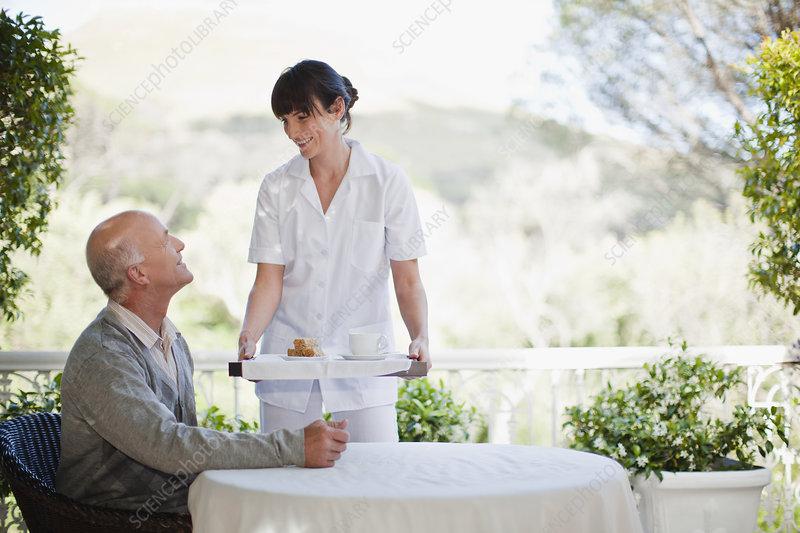 Waitress serving older man coffee