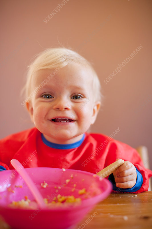 Smiling baby girl eating at table