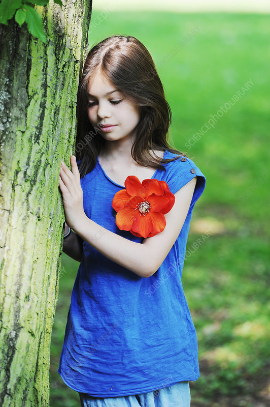Girl leaning against tree in park
