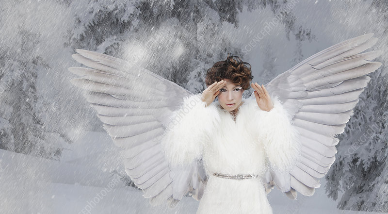 Woman wearing white wings in snow