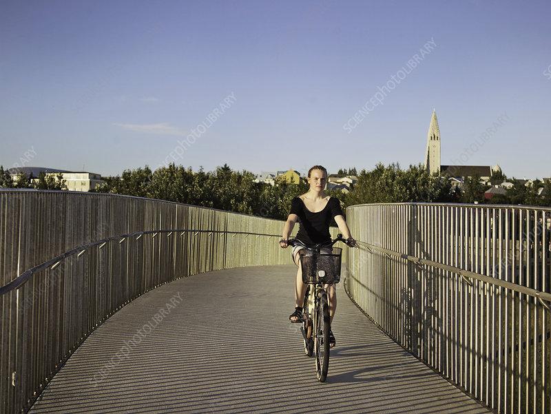 Woman riding bicycle on skybridge