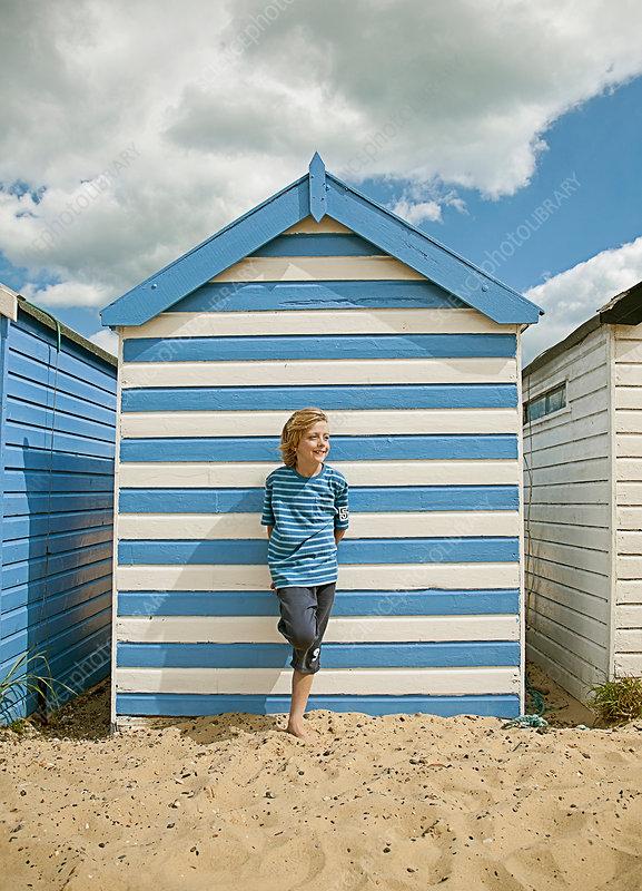 Boy leaning against shack on beach