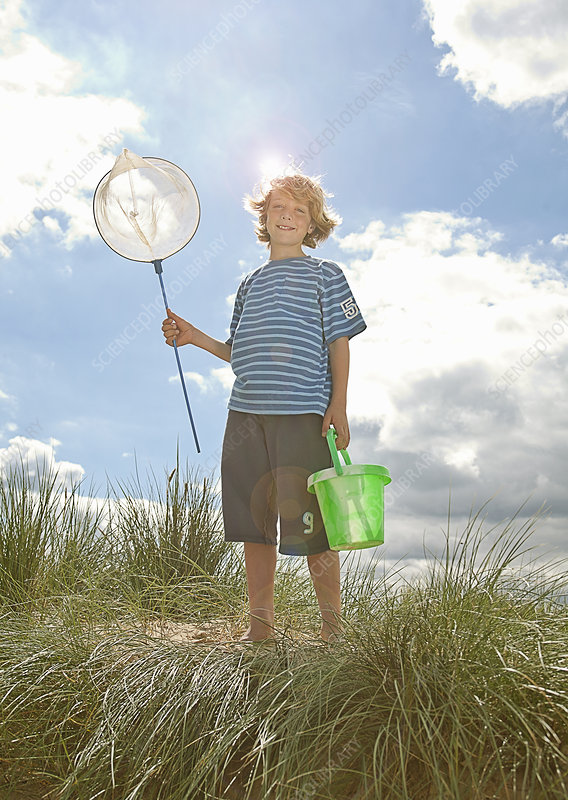 Boy carrying net and pail outdoors