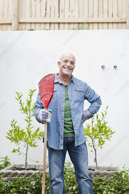 Older man holding rake in backyard