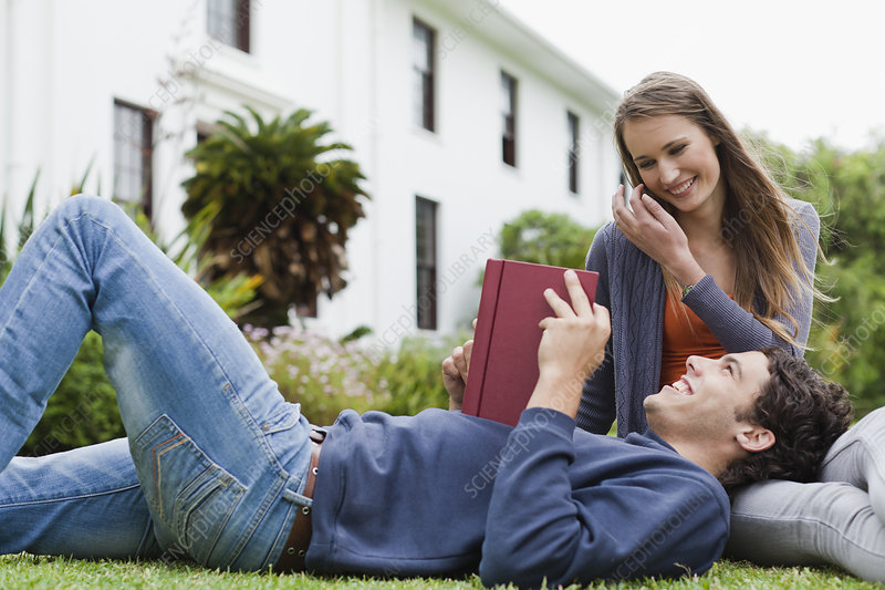 Student reading on grass on campus