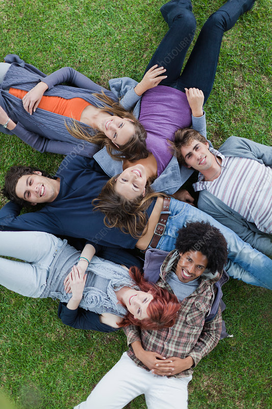 Students laying in grass on campus