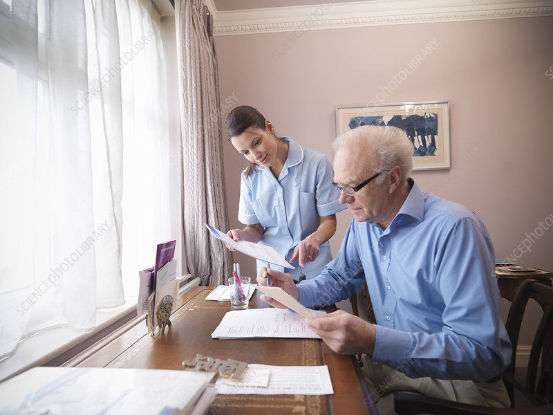 Older man and nurse reading papers