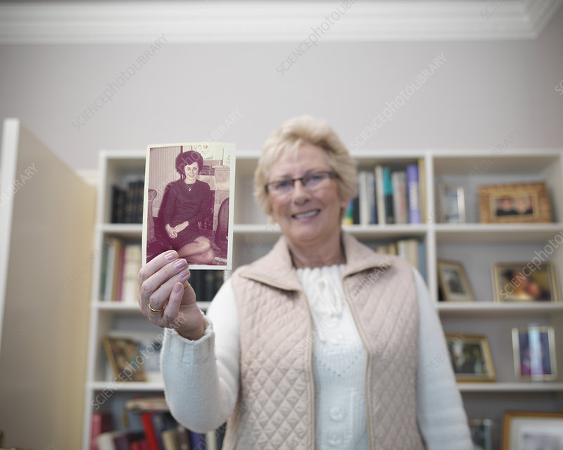 Older woman holding old photograph
