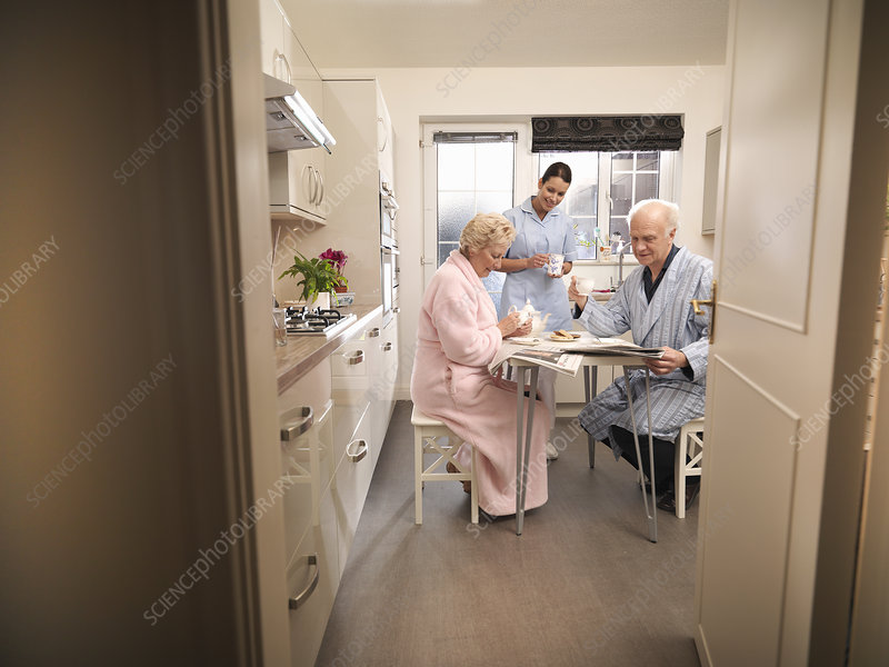 Nurse bringing older couple coffee
