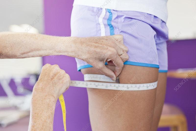 Trainer measuring girls leg in gym