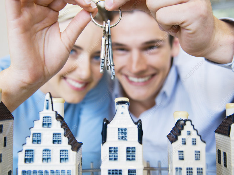 Couple with keys and model houses