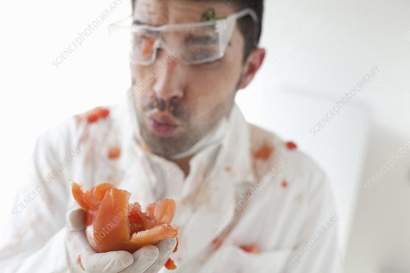 Scientist holding exploding tomato