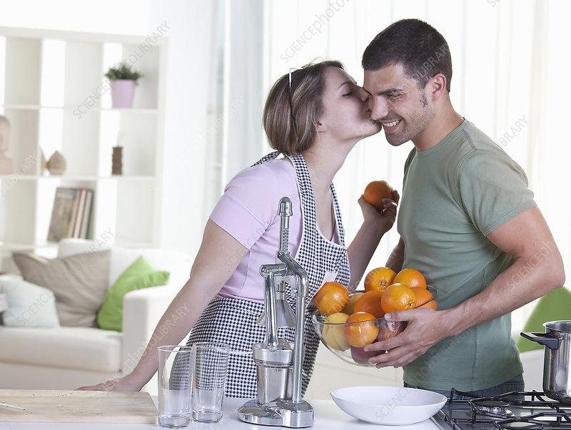 Woman kissing boyfriend in kitchen