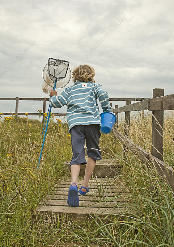 Boy carrying nets and pail outdoors