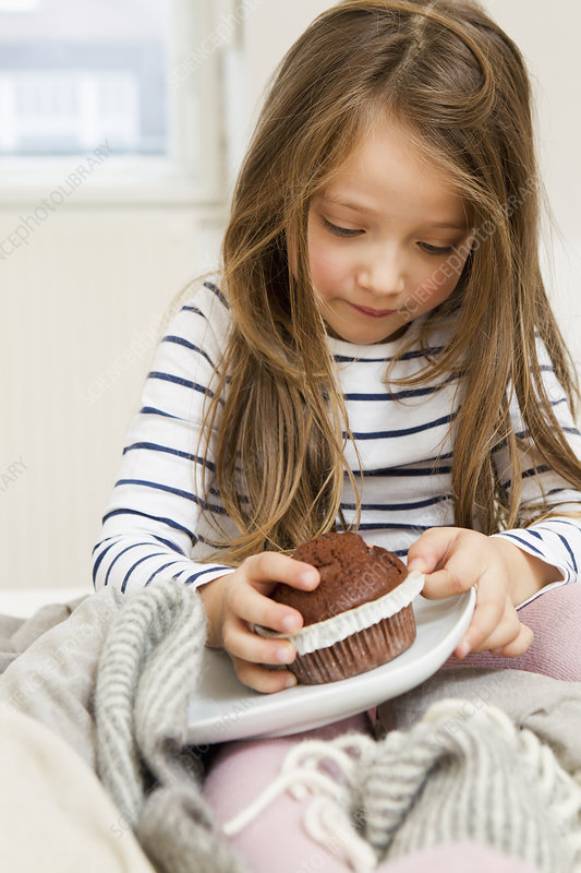 Girl eating chocolate muffin in bed