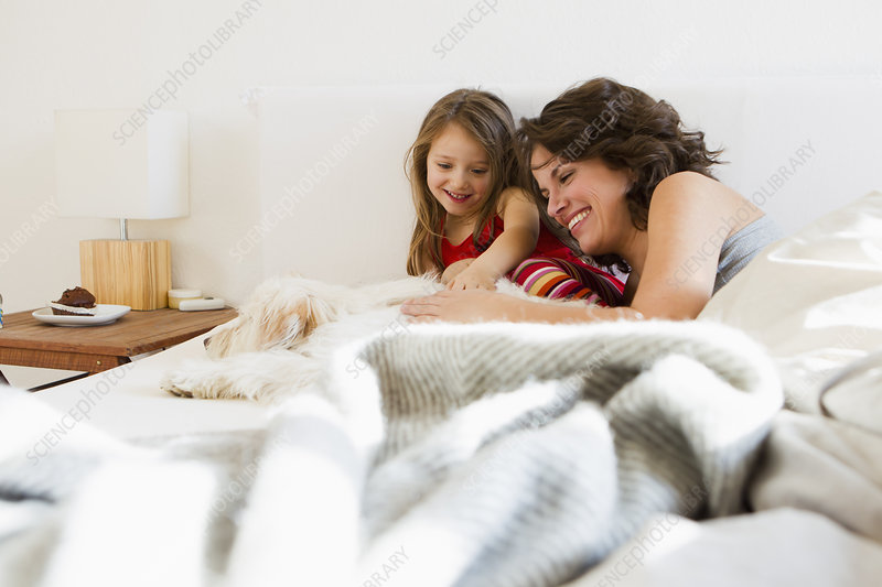 Mother and daughter in bed with dog