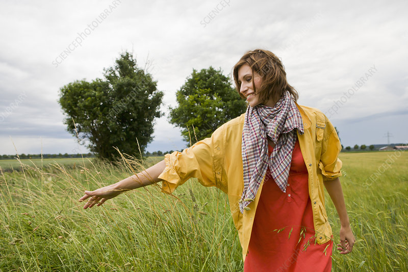 Smiling woman walking in tall grass