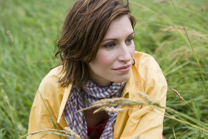 Smiling woman sitting in tall grass
