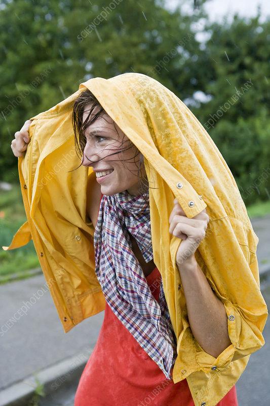 Smiling woman covering hair in rain