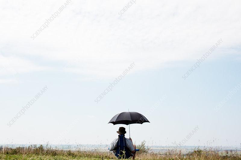 Man sitting under umbrella in field