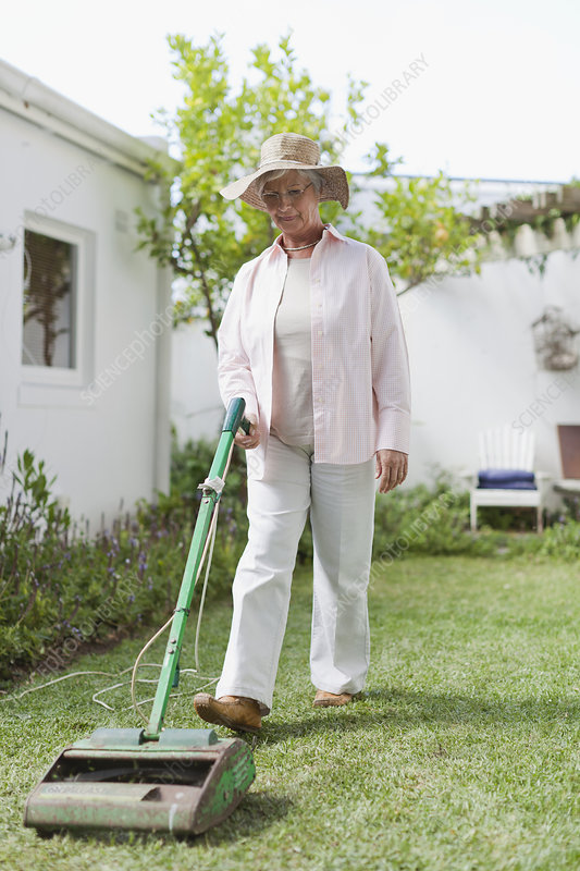 Older woman mowing lawn in backyard