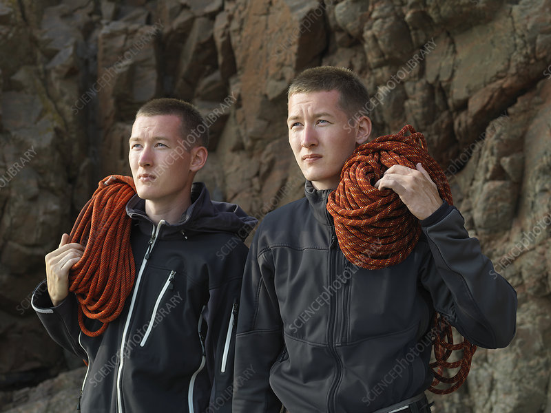 Men carrying loops of rope on beach