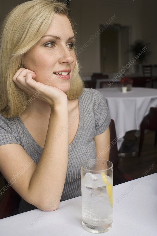 Woman having glass of water in cafe