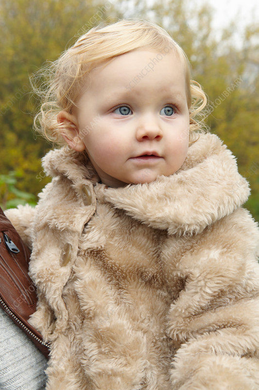 Toddler wearing fuzzy coat outdoors