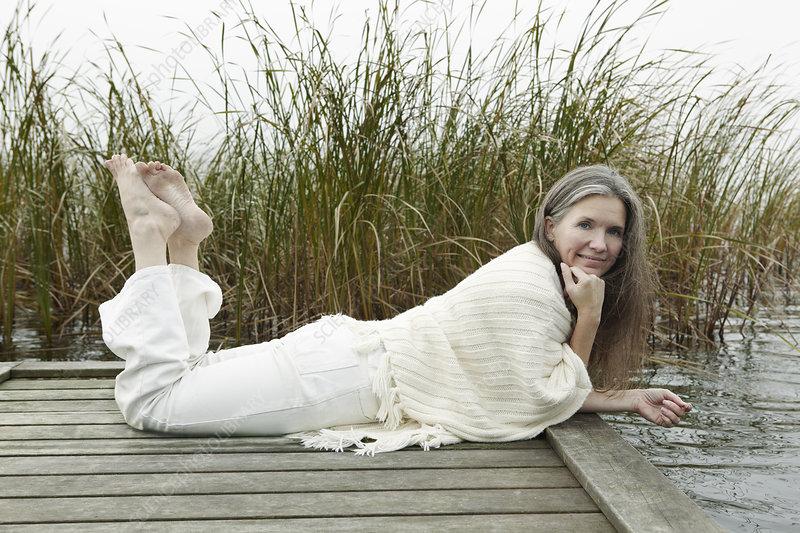 Older woman relaxing on wooden dock