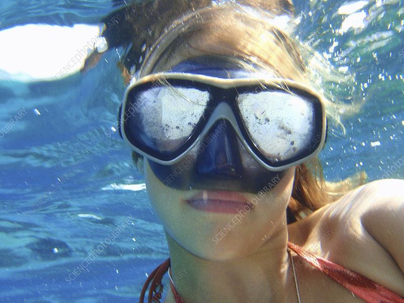 Teenage girl wearing mask underwater