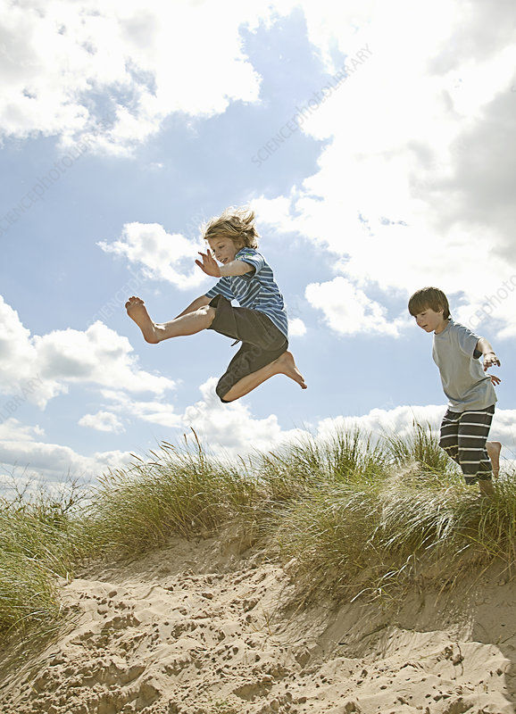 Children leaping over grass on beach
