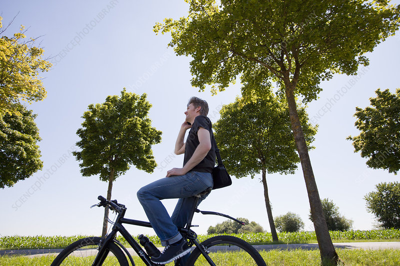 Man talking on cell phone on bicycle