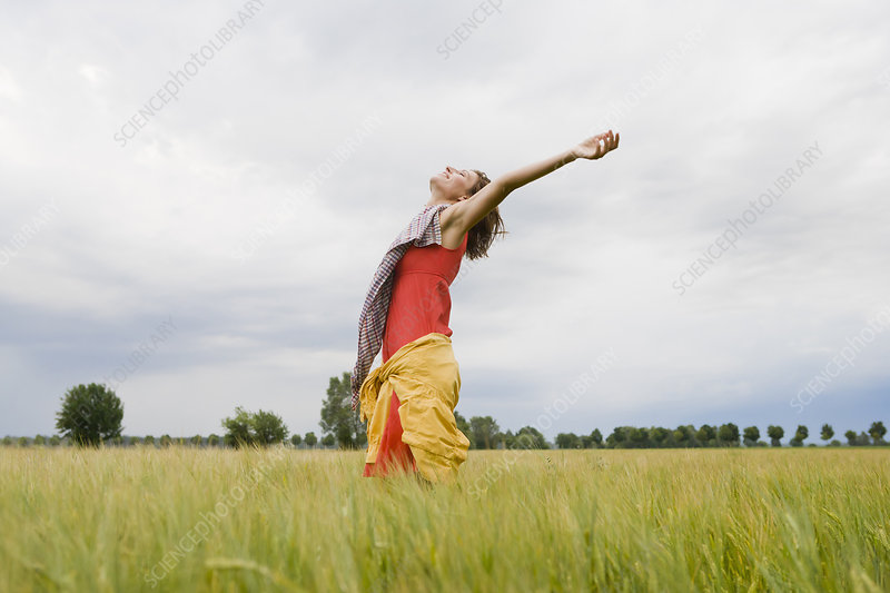 Smiling woman standing in tall grass