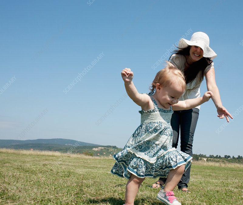 Mother and daughter walking in field