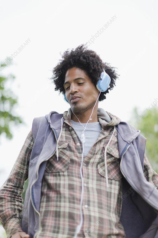 Man listening to headphones outdoors