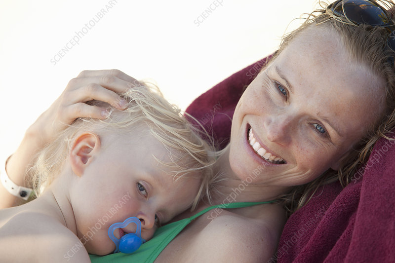 Smiling woman cuddling baby on beach