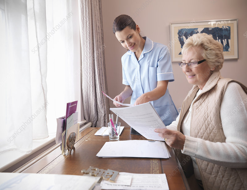 Older woman and nurse reading papers
