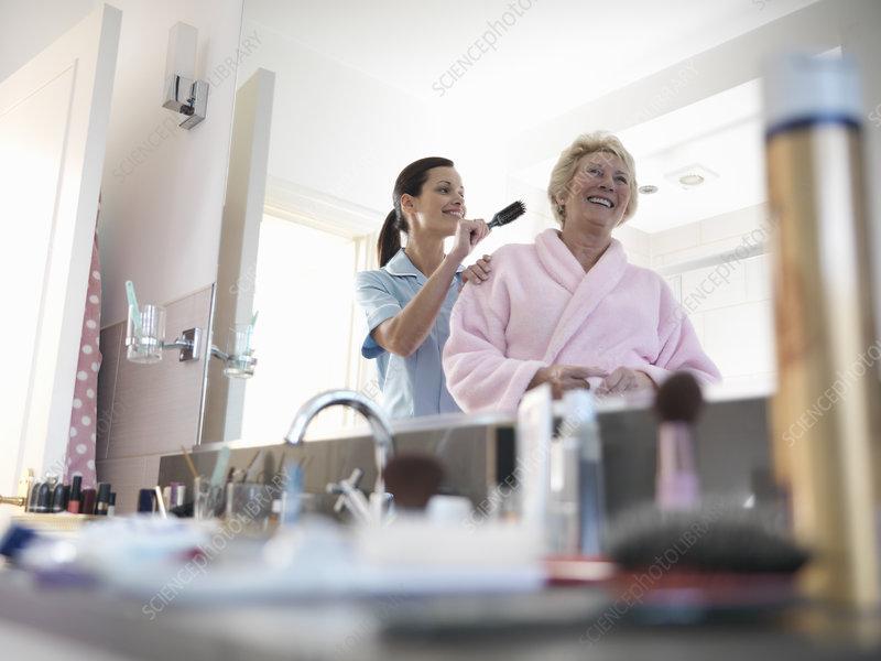 Nurse helping older woman brush hair