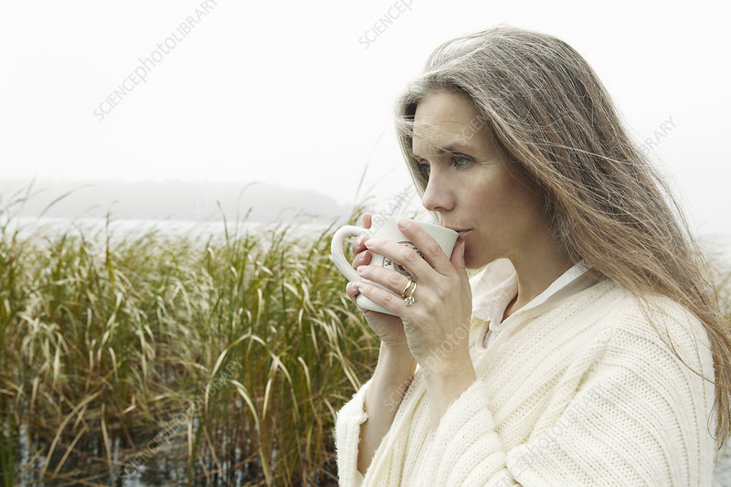 Older woman drinking coffee outdoors