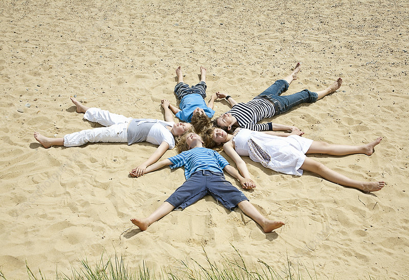 Children laying in formation on beach