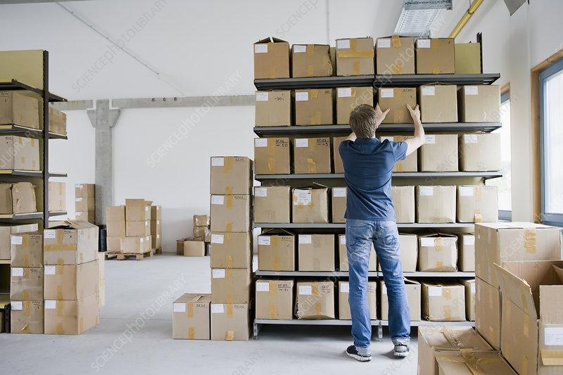 Man filing cardboard boxes in storage